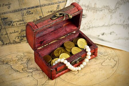 Treasure chest with coins on old adventure maps Stock Photo