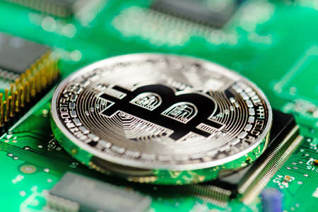 Silver Bitcoin virtual currency on a circuit board background Banco de Imagens - 82774067