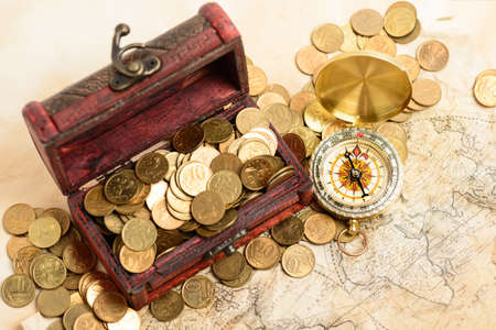 Open treasure chest filled with gold colored coins and compass over medieval world map