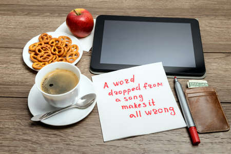 napkin handwriting message proverb on wooden table with coffee, some food and tablet PC A word dropped from a song makes it all wrong Stockfoto