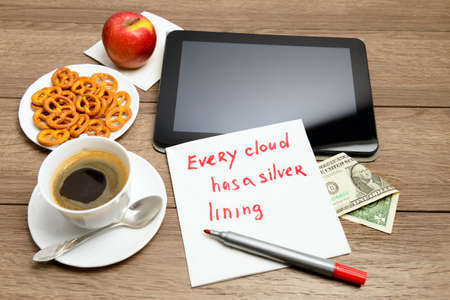 Wooden table with coffee, some food and napkin message proverbEvery cloud has a silver lining