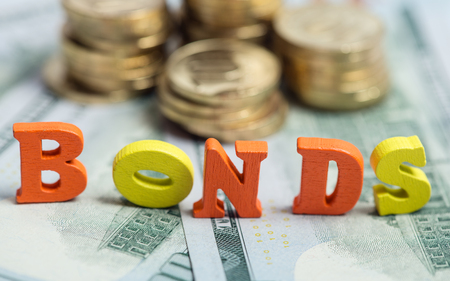 Bonds investment at wooden letters on US Dollar bills and golden coins Stok Fotoğraf