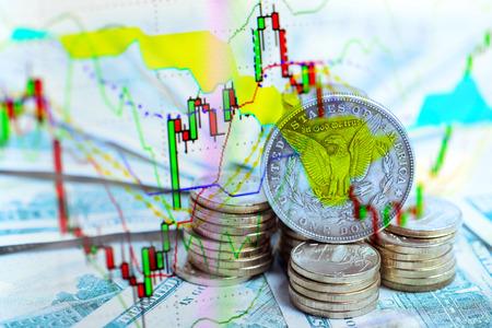 financieel en investeringsconcept - handelsgrafiek over zilveren dollarmuntstuk op Amerikaanse dollarbiljetten en hoop gouden munten Stockfoto