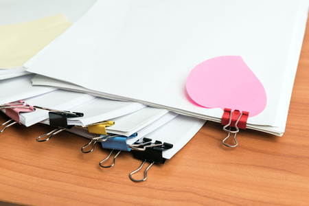 Pile of unfinished documents on office desk, one with heart shape sticker Stock Photo