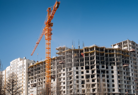 Construction site background. Hoisting cranes and new buildings