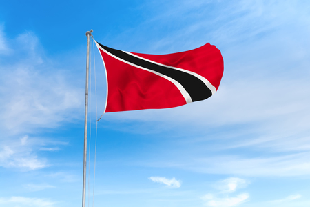 Trinidad and Tobago flag blowing in the wind over nice blue sky background Imagens