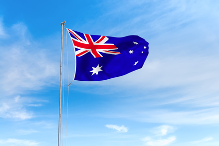 Australia flag blowing in the wind over nice blue sky background
