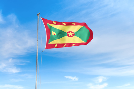 Grenada flag blowing in the wind over nice blue sky background Stock Photo