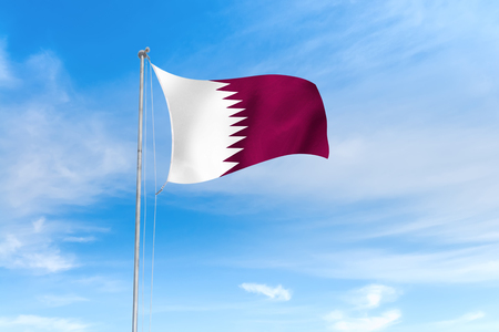 Qatar flag blowing in the wind over nice blue sky background