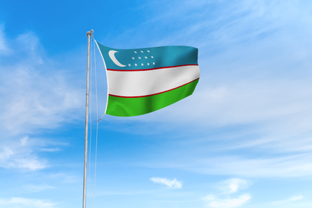 Uzbekistan flag blowing in the wind over nice blue sky background