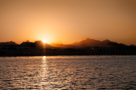 Beautiful sunset landscape at black sea and mountain above orange sky with sun reflection Stock Photo - 129882869