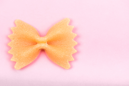 Farfalle tie bow shaped pasta macro on pink background isolated with clipping path