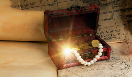 Old pirate chest on vintage maps and scrolls  with sparkling treasure
