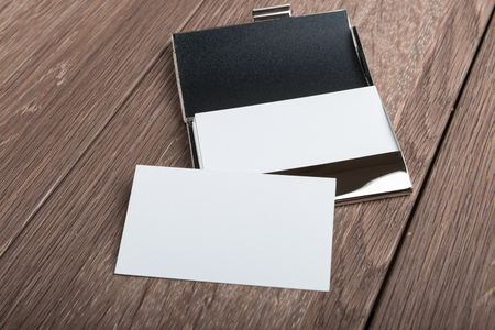 Business card mockup on wooden table. Single and in card holder