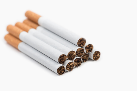 Pile of ten cigarettes on white background. The risk of illness is significantly reduced if you smoke less than 10 cigarettes per day