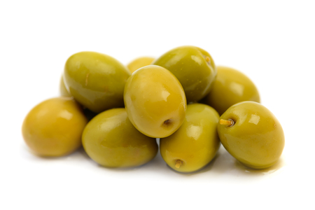 Pile of wet green olives macro in brine drops isolated on white background Stock Photo