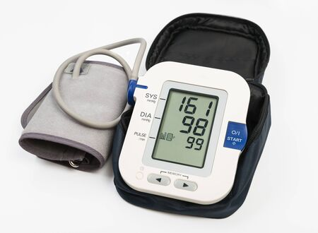 Electronic blood pressure meter and cuff in case. Meter display showing high blood pressure 151/98. Clipping path Imagens