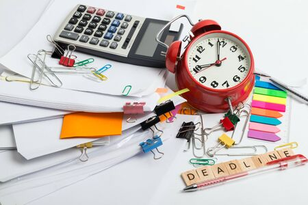 Pile of documents, alarm clock, calculator and office stuff - time management concept Imagens