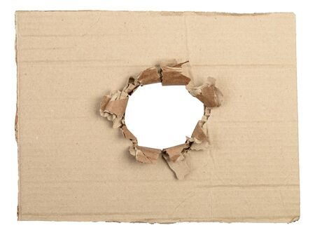 Ripped hole in cardboard package. Isolated on white