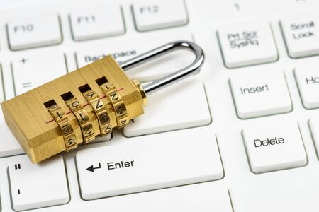 Computer security concept with combination lock padlock on white keyboard Imagens