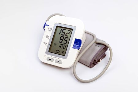 Electronic blood pressure meter monitor and cuff on white background Imagens
