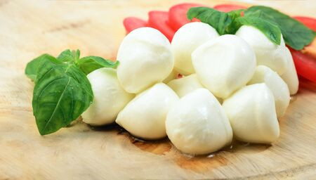 Mozzarella cheese with tomatoes and basil on wooden desk