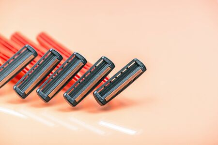 Group of red safety razors on orange color background.  Many Shave blade razors on red surface