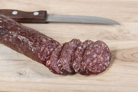 Dry fat salami sausage stick and knife on wooden board with slices. Close-up. top view