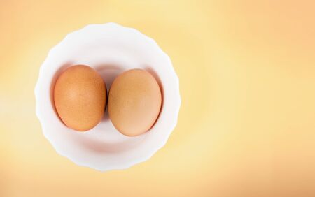 Pair of brown eggs in white bowl on pastel yellow background with copyspace. Clipping path for easy cut out for replace background Imagens