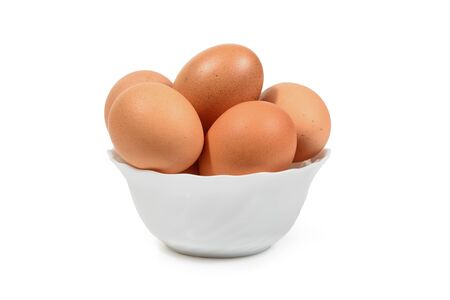 Brown eggs in white porcelan bowl isolated. Clipping path for easy cut out. Imagens