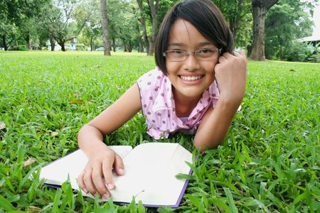Young girl reading in the park. 스톡 콘텐츠