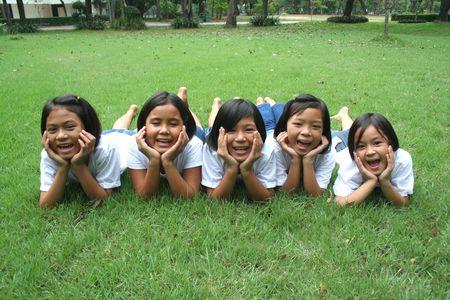 Vijf kinderen die spelen in het park.