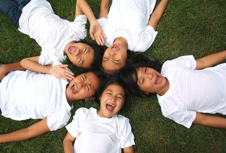 Vijf kinderen spelen in het park.  Stockfoto
