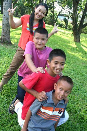 Vier kinderen spelen in het park.  Stockfoto