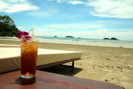 Long Island Ice-tea with beautiful tropical beach background.