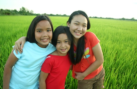 Portrait of three girls in the rice field.  photo