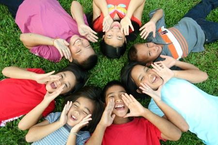 interracial: Sieben Kinder spielen im Park.  Lizenzfreie Bilder