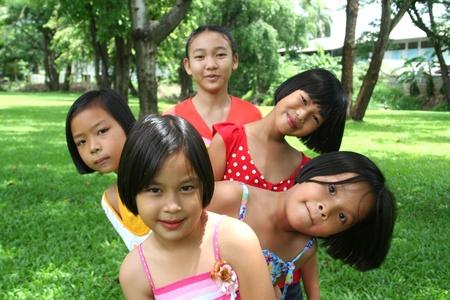 ni�os chinos: Cinco ni�os jugando en el parque.  Foto de archivo