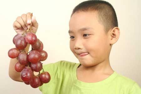 grape seed: Portrait of young boy with grapes