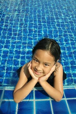 niños nadando: Chica joven que tiene buen tiempo en la piscina Foto de archivo