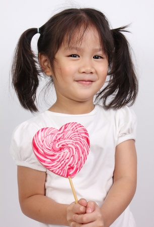 Young girl holding lollipop  photo