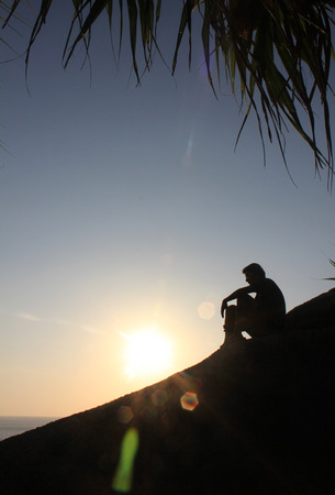 only young men: Man sitting as silhouette by the sea