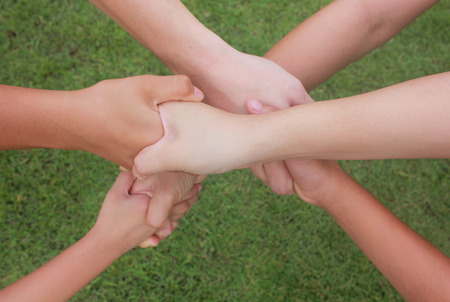 combining: Multicultural hands, hands with green grass background. Stock Photo