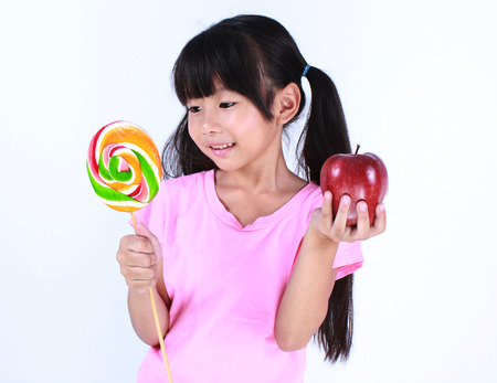 deciding: Cute young girl with one lollipop and one apple over white background Stock Photo