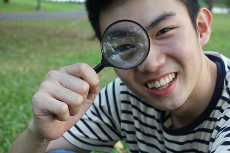 Young man with magnify glass photo