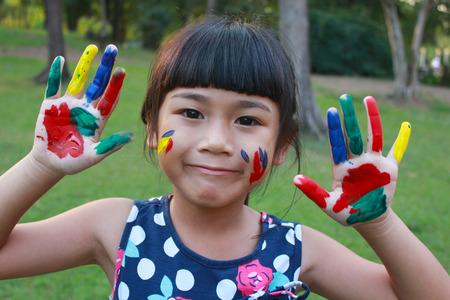 ni�os estudiando: Linda chica con las manos en la pintura Foto de archivo