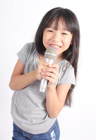 cantando: Niña bonita con el micrófono en la mano