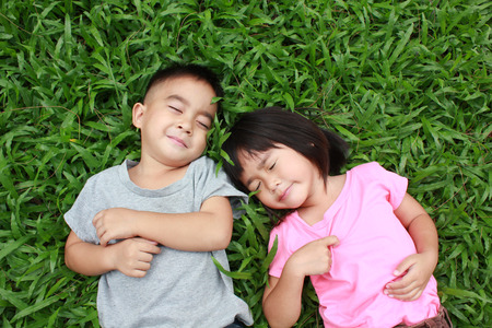 Two kids sleeping in the park.