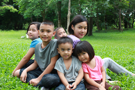 smiling faces: Six asian kids having a good time in the park.