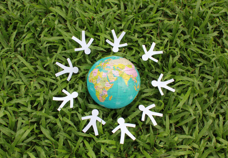 team hands: Paper people in a circle around the world with green grass background.